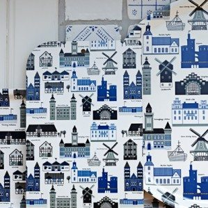 "Mitt Skåne trays and cuttingboards with characteristic buildings such as churches, ""möllor"" as well as halftimbred houses from all over, in the south of Sweden, in blue. Here you will find Malmö, Helsingborg, Lund and Kristianstad... in this pattern design. Here is a summer fresh picture of Mitt Skåne with beautiful tiles behind. You can also buy Mitt Skåne as textile products like aprons and fabrik from Klippan Yllefabrik."