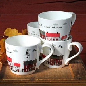 Eksjö mugg i benporslin med motiv av Eksjös fina hus och byggnader i rött.Eksjö mug in bone china with a surface pattern of Eksjös beautiful houses in red.